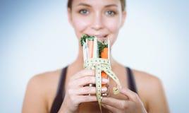 Vrouwenholding het drinken glashoogtepunt van verse fruitsalade met een meetlint rond het glas Stock Afbeelding