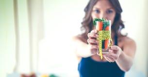 Vrouwenholding het drinken glashoogtepunt van verse fruitsalade met een meetlint rond het glas Stock Foto