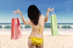 Vrouwenholding het winkelen zak bij strand stock foto's