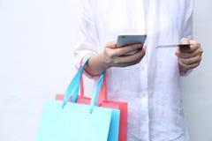 Vrouwenholding het winkelen zak en het gebruiken van smartphone die geld langs betalen Royalty-vrije Stock Fotografie