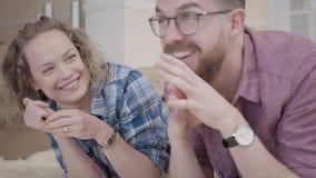 Vrouwenholding sleutel en het glimlachen Jonge familie die op pluizig tapijt dicht omhoog met dozen in de achtergrond liggen Gehu stock video
