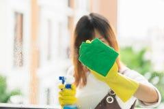 Vrouwenhuishoudster die de spiegel met gele doek schoonmaken Royalty-vrije Stock Afbeelding
