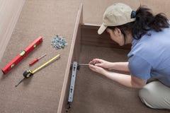 Vrouwenhuisvrouw het samenbrengen assembleert bedkader, gebruikend hand Royalty-vrije Stock Foto