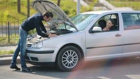 Vrouwenhulp aan man reparatie gebroken auto stock videobeelden