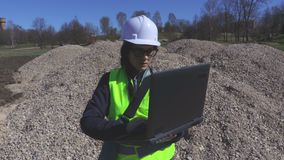 Vrouweningenieur die laptop met behulp van bij de grintstapel stock video