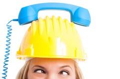 Vrouweningenieur die met telefoonontvanger op hoed kruiselings kijken Stock Afbeeldingen