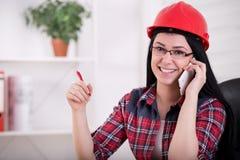 Vrouweningenieur die op de telefoon in het bureau spreken Royalty-vrije Stock Afbeeldingen