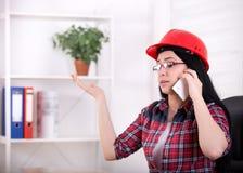 Vrouweningenieur die op de telefoon in het bureau spreken Royalty-vrije Stock Foto's