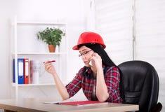 Vrouweningenieur die op de telefoon in het bureau spreken Stock Afbeeldingen