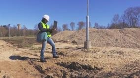 Vrouweningenieur het inspecteren bouwwerf en het gebruiken van laptop stock video
