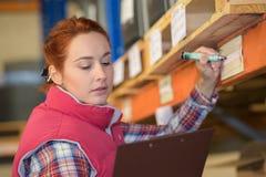 Vrouweninspecteur die inventaris in pakhuis doen royalty-vrije stock foto
