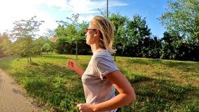 Vrouwenjogging in de zon stock footage