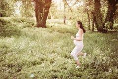 Vrouwenjogging op gebied Jonge vrouw in weide Stock Afbeelding