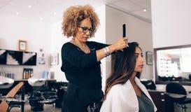 Vrouwenkapper aan het werk in salon stock fotografie
