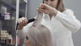 Vrouwenkapper die kapsel met behulp van het strijken doen stock video