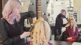 Vrouwenkapper die krullen maken bij blond haar met het krullen van ijzers bij schoonheidssalon Stock Foto's