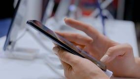 Vrouwenklant die nieuw model van smartphone in elektronische winkel testen stock video