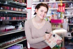 Vrouwenklant die over compact poeder in winkel beslissen stock afbeelding