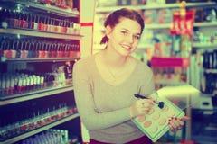 Vrouwenklant die over compact poeder in winkel beslissen stock foto