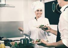 Vrouwenkok die aan serveerster klaar om salade te dienen geven Royalty-vrije Stock Foto's