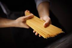 Vrouwenkok die ruwe spaghetti op een donkere achtergrond houden Traditioneel Italiaans voedsel royalty-vrije stock foto