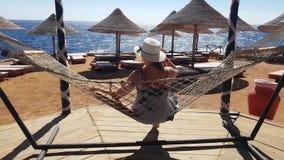 Vrouwenkou in de hangmat op het strand, vakantie op het overzees, die op het strand, het overzees en de recreatie, het zand en he stock video