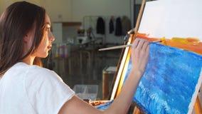 Vrouwenkunstenaar die een beeld op schildersezel met olieverven in haar workshop schilderen stock video