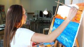 Vrouwenkunstenaar die na haar inspiratie haar nieuw beeld schilderen bij nacht in haar workshop stock videobeelden