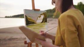 Vrouwenkunstenaar het schilderen landschap openlucht stock video