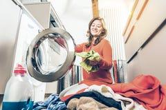 Vrouwenlading die machineWoman Ladings Vuile Kleren in Wasmachine voor Was wassen stock afbeeldingen