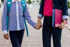 Vrouwenleraar en studentenholdingshanden, openluchtachtergrond stock foto's