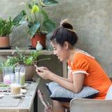 Vrouwenlevensstijl die een mobiele telefoon in koffiekoffie met behulp van Stock Foto's
