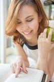 Vrouwenlezing en holding een appel Royalty-vrije Stock Foto