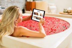 Vrouwenlezing op tablet terwijl het nemen van bad royalty-vrije stock fotografie