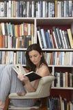 Vrouwenlezing tegen Boekenrekken stock fotografie