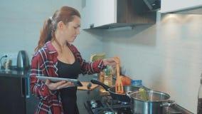 Vrouwenmamma het koken in het keukenconcept kookt soep in een pan en bekijkt het recept op een digitale tablet Meisjesmoeder stock video