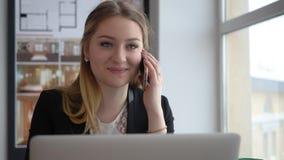 Vrouwenmanager die door mobiele telefoon spreken die aan laptop in bedrijfsbureau werken stock videobeelden