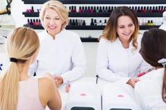 Vrouwenmanicures die vrouwelijke cliënten manicuring stock afbeeldingen