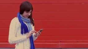 Vrouwenmeisje die een smartphone in een jasje en a houden stock footage