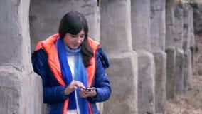 Vrouwenmeisje die een smartphone in jasjesjaal houden stock videobeelden