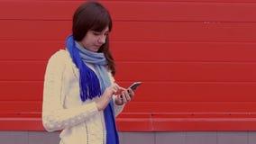 Vrouwenmeisje die een smartphonetelefoon in een jasje en een sjaal sociale netwerkenmedia houden stock videobeelden