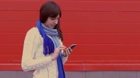 Vrouwenmeisje die een smartphonetelefoon in een jasje houden stock video