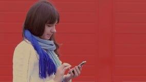 Vrouwenmeisje die een smartphonetelefoon in jasje houden stock videobeelden