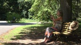 Vrouwenmeisje die met laptop aan parkbank werken die draadloze Internet-verbindingsproblemen hebben 4K stock videobeelden