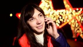 Vrouwenmeisje die op telefoon bij nacht op a spreken stock video