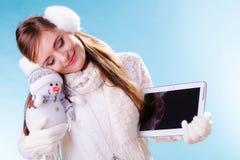 Vrouwenmeisje met tablet en weinig sneeuwman De winter Stock Foto