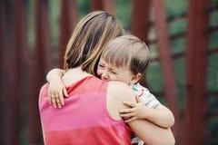 Vrouwenmoeder die haar troosten die weinig zoon van de peuterjongen schreeuwen stock fotografie