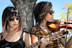 Vrouwenmusici die gitaar en viool in openlucht spelen royalty-vrije stock afbeelding