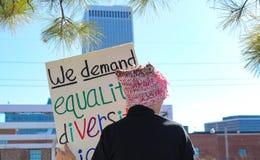 Vrouwenn roze pussy hoed met terug naar cameratribunes tegen stadshorizon met teken eisen wij Gelijkheidsdiversiteit bij Vrouwen stock fotografie