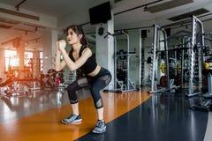 Vrouwenoefening die hurkende training doen bij gymnastiekgeschiktheid stock afbeeldingen